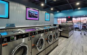 LaundryMax laundromat interior: gleaming row of Dexter washers